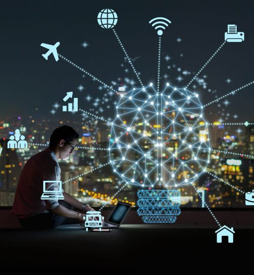 Polygonal brain shape of an artificial intelligence with various icon of smart city Internet of Things Technology over Asian businessman sitting and using the laptop over the cityscape background